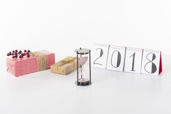 close up view of blank calendar, sand clock and wrapped gifts isolated on white